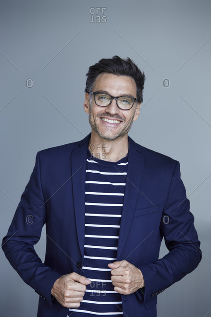 Portrait of laughing businessman with stubble wearing blue suit coat and glasses