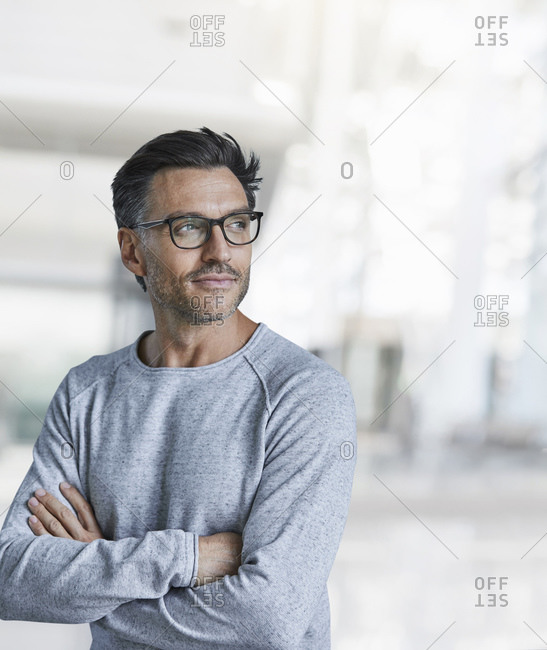 Portrait of content mature man with stubble wearing glasses