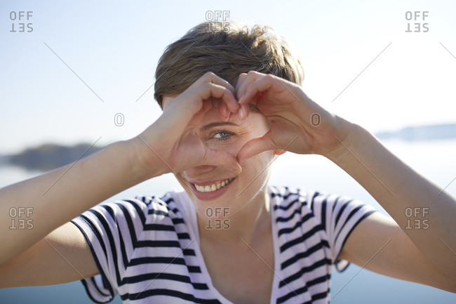 Portrait of smiling woman in front of lake shaping heart with her fingers