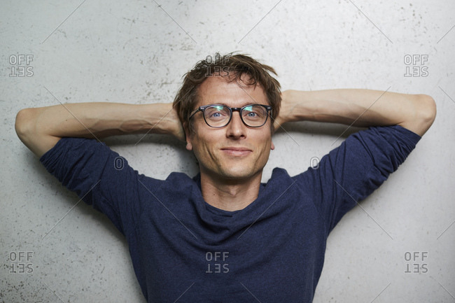 Portrait of smiling man with hands behind head wearing glasses