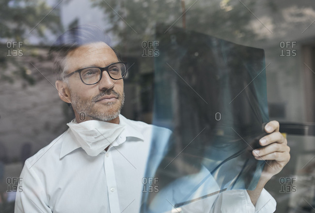 Portrait of radiologist behind windowpane looking at x-ray image