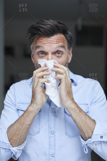 Portrait of man blowing nose