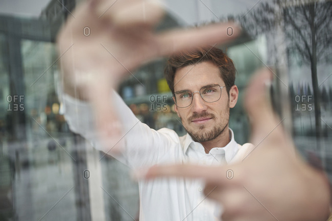 Portrait of young businessman behind glass pane shaping a finger frame