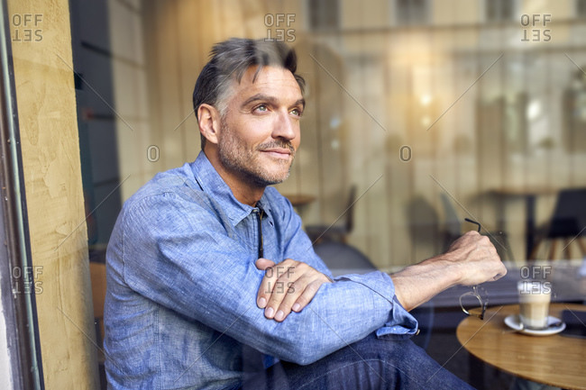 Portrait of man behind windowpane in a cafe