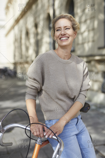 Portrait of happy woman with bicycle in the city