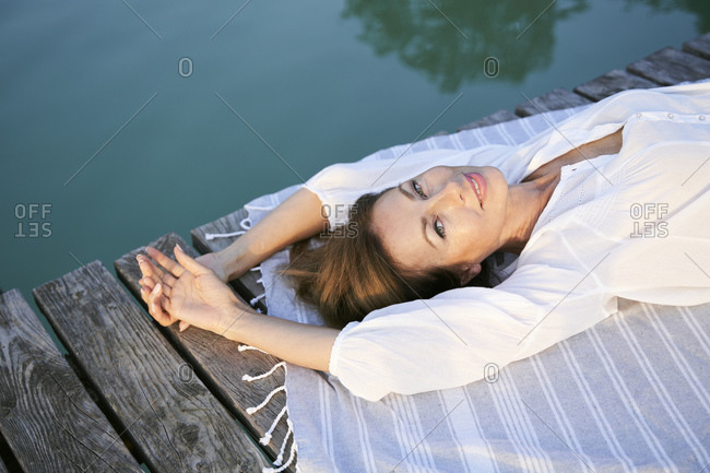 Portrait of smiling mature woman lying on a towel on a jetty at a lake