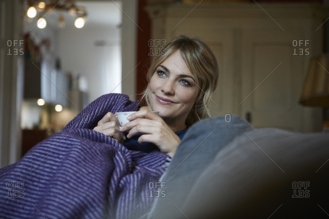 Portrait of smiling woman with cup of tea relaxing on couch at home