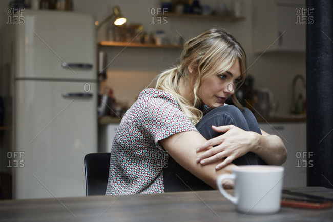 Portrait of pensive woman sitting at table in the kitchen