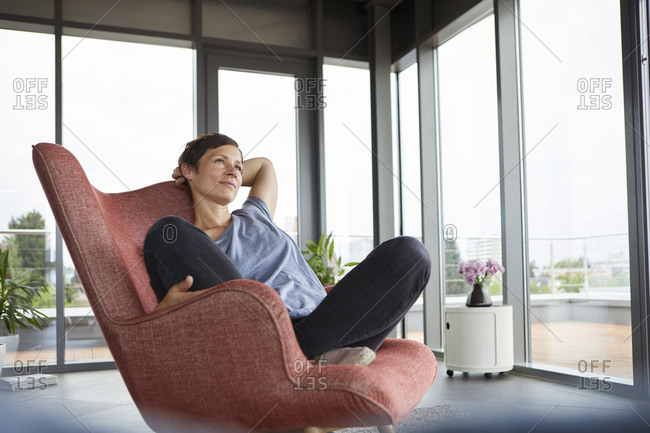 Woman sitting in armchair at home relaxing