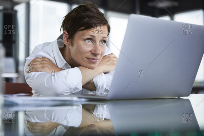 Businesswoman leaning on glass table in office looking at laptop
