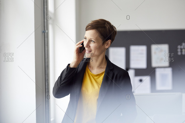Attractive businesswoman standing in office- using smartphone
