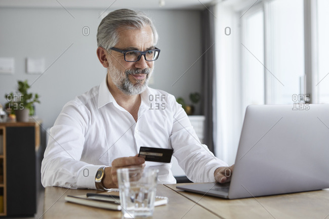 Portrait of content mature man paying online with credit card at home