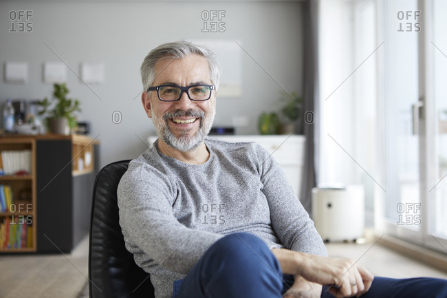 Portrait of content mature man in his living room