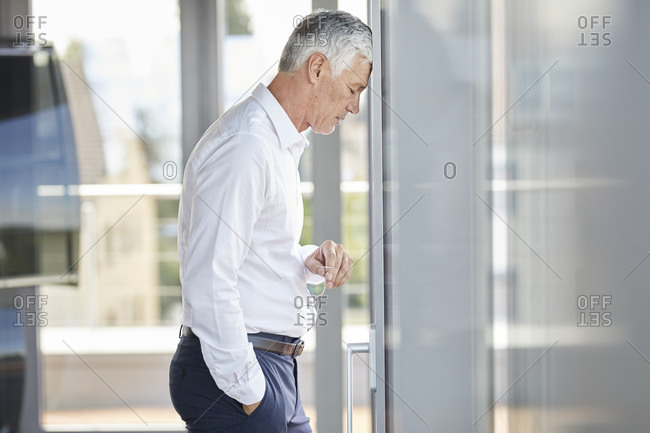 Exhausted businessman resting head on windowpane