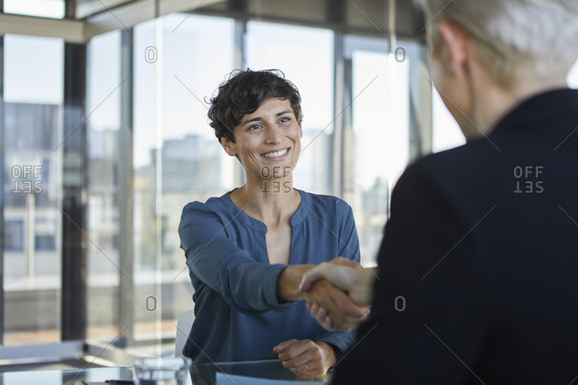 Two businesswomen shaking hands at desk in office