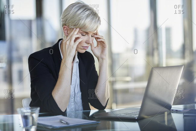 Exhausted businesswoman sitting at desk in office with closed eyes