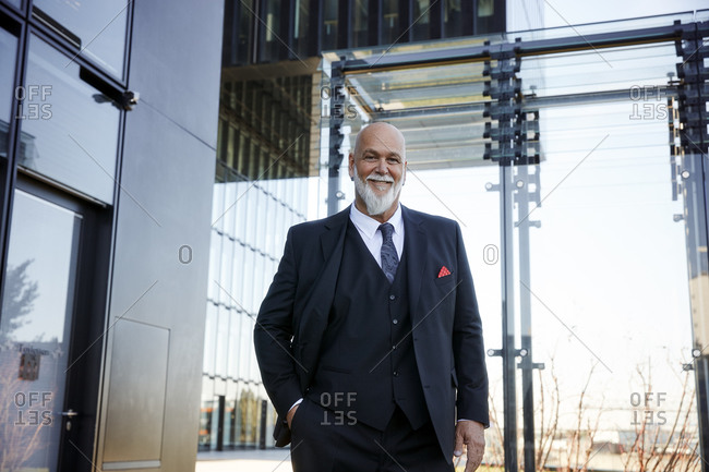 Elegant businessman standing in front of office building- smiling