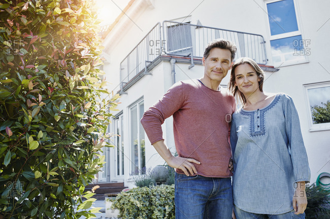 Portrait of couple in front of their home
