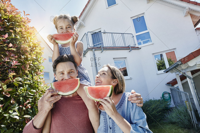 Portrait of happy family with slices of watermelon in front of their home