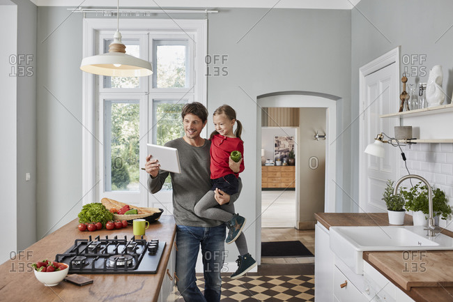 Happy father and daughter with bell pepper and tablet in kitchen