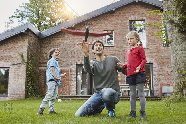 Father with two children playing with toy airplane in garden of their home