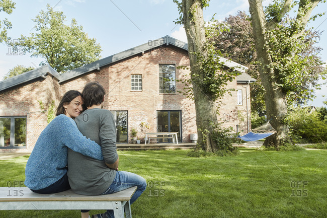 Smiling affectionate couple sitting in garden of their home