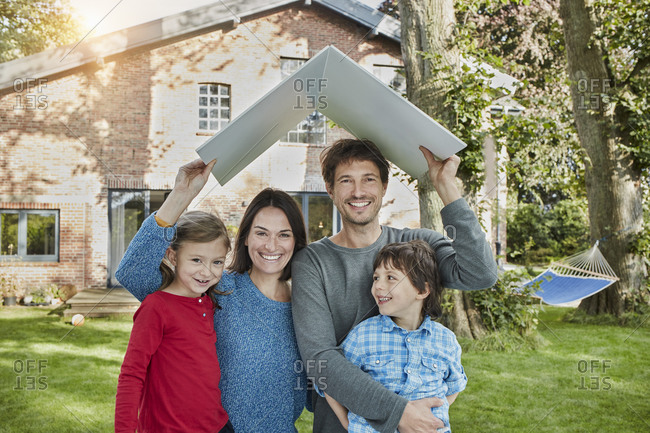 Portrait of happy family in garden of their home holding roof