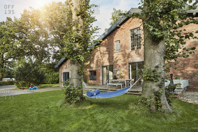 Residential house with hammock in garden and girl playing in background