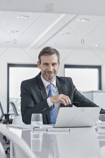 Portrait of confident businessman with laptop at desk in office