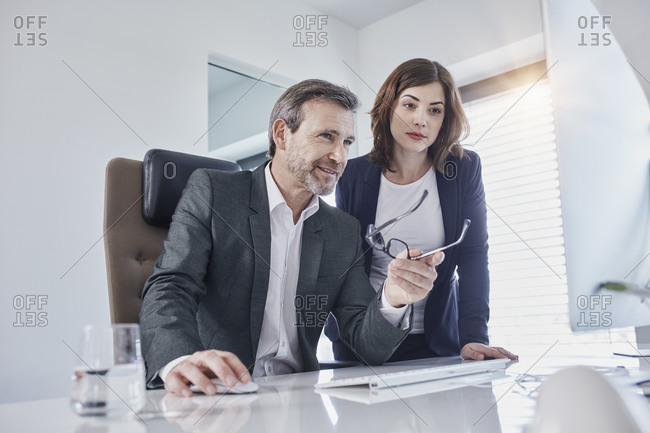 Businessman and businesswoman discussing at desk in office