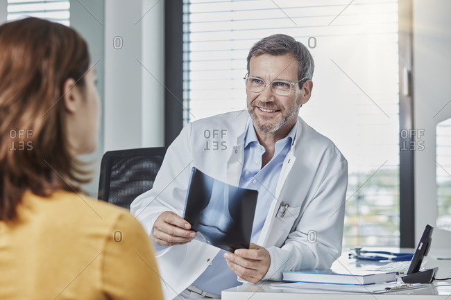 Physician patient talk- doctor holding x-ray image