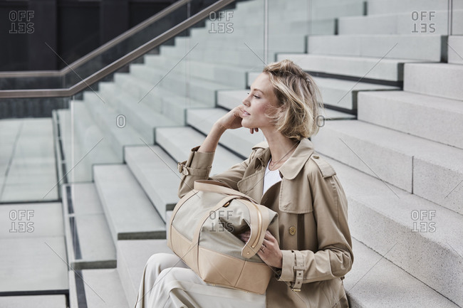 Fashionable blond businesswoman wearing beige trench coat sitting on stairs with travelling bag
