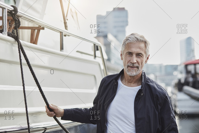 Confident mature man at a marina next to a yacht