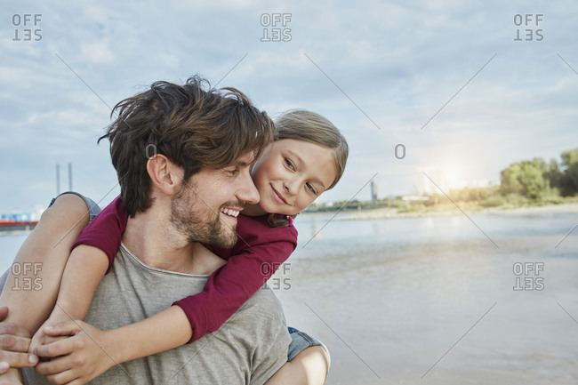 Germany- Duesseldorf- happy father carrying daughter piggyback at Rhine riverbank