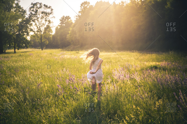 Back view of girl running on flower meadow at evening twilight