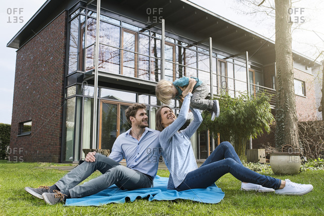 Happy parents with son sitting on blanket in garden in front of their home