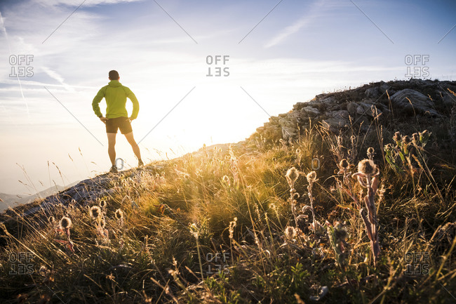 Italy- mountain running man standing on trail looking at sunset