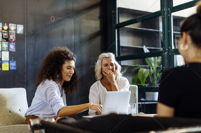 Happy businesswomen with laptop working together in loft office