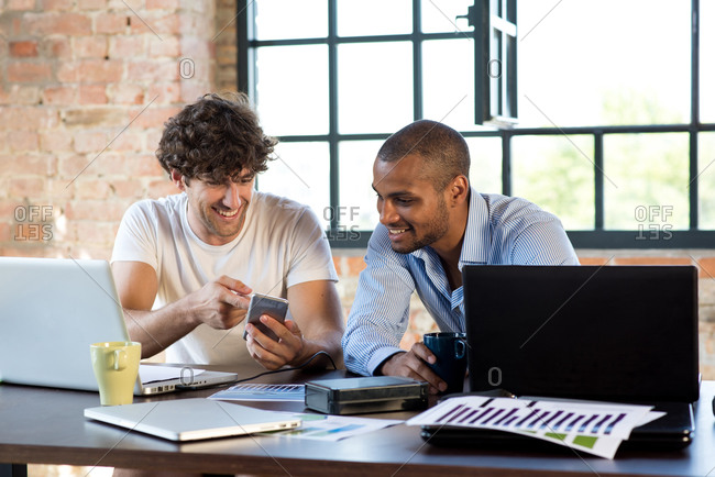 Two young businessmen working together in co-working space- using laptops