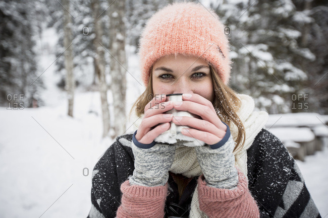 Portrait of young woman drinking hot drink outdoors in winter
