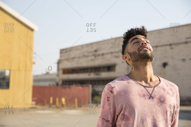 Young man outdoors leaning back