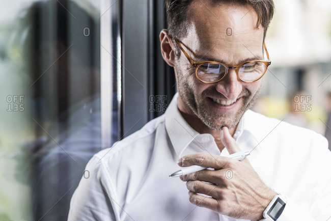 Portrait of laughing businessman wearing glasses and smartwatch