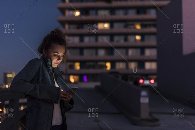 Young woman in the city checking cell phone in the evening