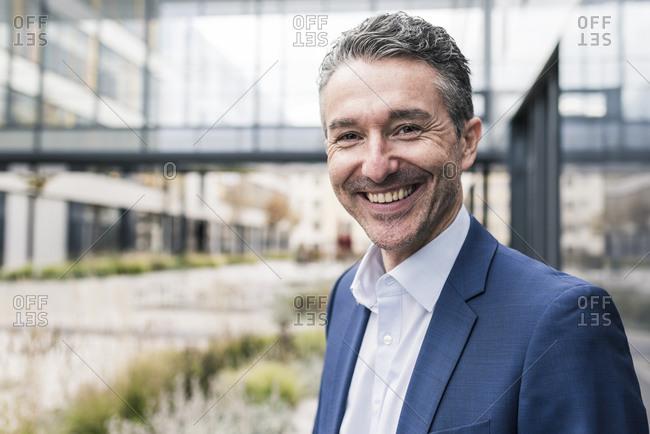 Portrait of smiling businessman outside office building