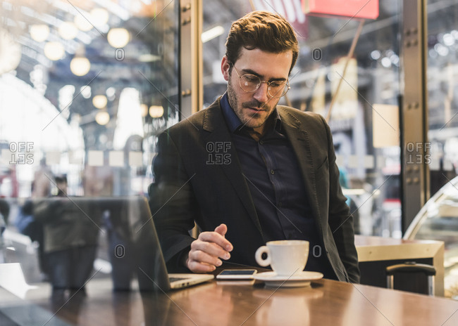 Young businessman in a cafe at train station with cup of coffee- laptop and cell phone