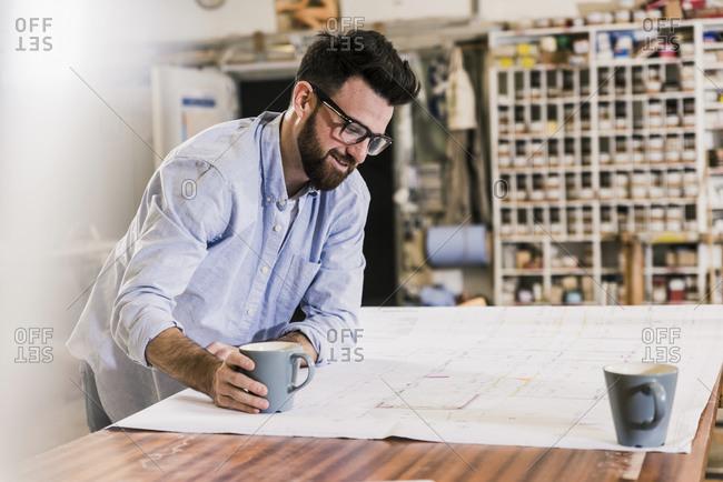 Smiling man looking at construction plan