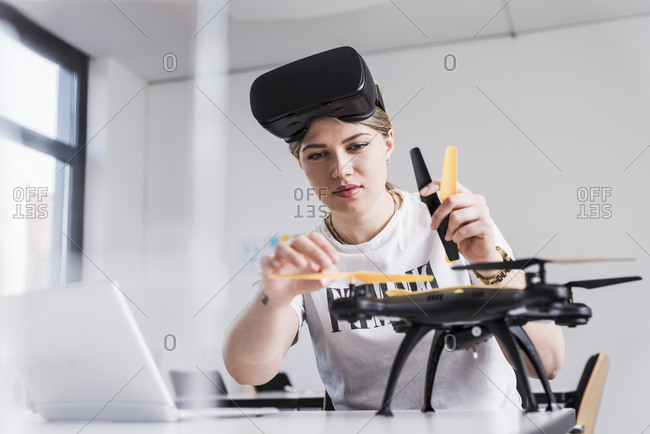Young woman with laptop and VR glasses at desk examining drone