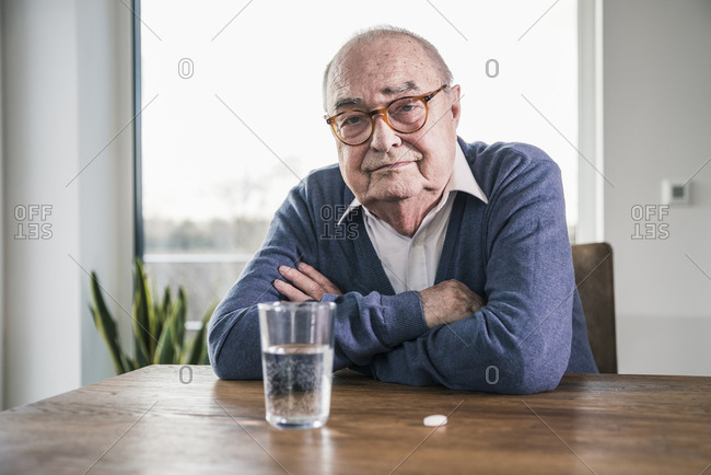 Portrait of senior man sitting at table with pill and glass of water