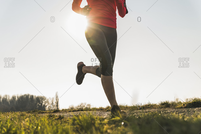 Low section of woman running on rural path