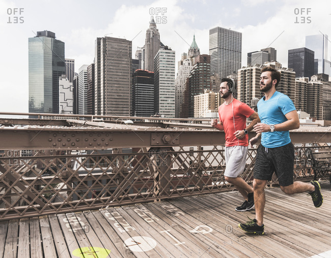 USA- New York City- two men running on Brooklyn Bridge with data on the ground